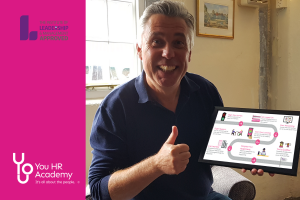 Ian Mundy, Corporate and Strategy Manager, You HR, holding a tablet showing the learner journey for a TILM approved learner taking one of You HR's People Management Courses